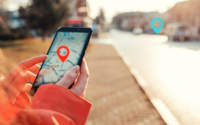 Concept of Internet maps and navigation. Female hands hold smartphone with maps app, and marked location icon, red and blue destination icon.